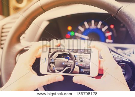 smart car concept - driving wheel and hands holding phone with augmented reality ap, retro toned
