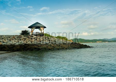 Hut on a rocky outcrop in the middle of the sea. The blue water and sky make this a perfect place to spend a relaxing day