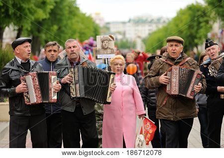 Orel Russia - May 9 2017: Victory Day selebration. Senior men singing playing accordions and walking on street