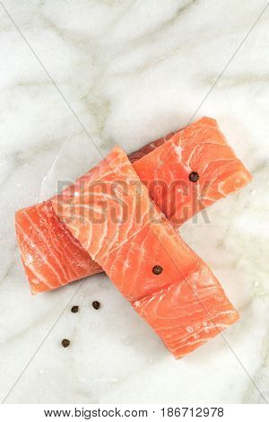An overhead photo of two slices of salmon on a white marble table with a place for text, with salt and pepper