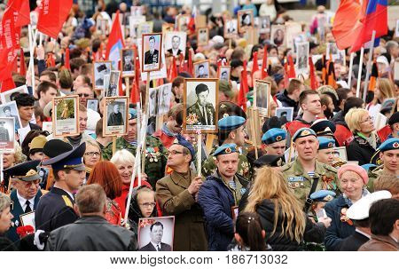 Orel Russia - May 9 2017: Victory Day selebration. Big crowd of people holding red Soviet flags and portraits of hero ancestors in Immortal Regiment crowd