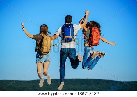 women and handsome man jumping on mountain top on blue sky. Three friends or tourists with colorful backpacks on idyllic sunny day. Back view. Summer vacation. Traveling. Success