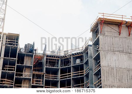 skeleton model of a house made of concrete panels and bricks with builders on the top floor. The concept of erection of apartment buildings.
