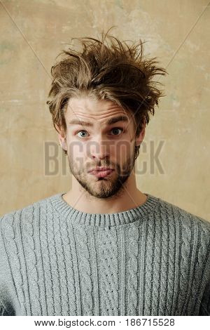 Male beauty and hairdressing. Handsome bearded man with beard or surprised sexy caucasian macho on beige wall background. Stylish blond hair haircut and young unshaven face skin