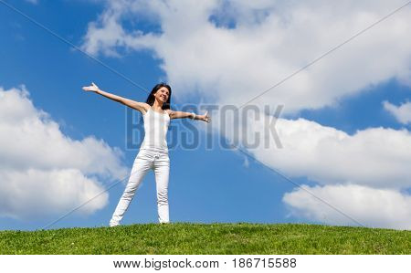 Happy young woman dreams to fly on winds. Landscape of grass field on bright sunny day. Nature beauty background, blue cloudy sky and summer green meadow. Outdoor lifestyle. People freedom concept