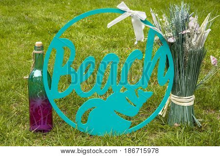 A beach sign with a wine bottle and centerpiece