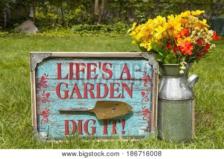 A garden themed still life with a sign and a milk can full of flowers