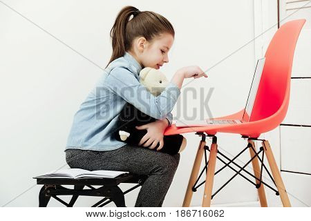 Child Or Cutegirl Hugging Teddy Bear And Typing On Laptop