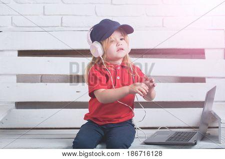 Little Kid Wearing Headphone Near Laptop On White Background