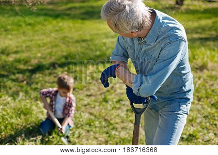 Young generation. Senior gardener wearing navy blue gloves leaning on a spade and gazing his adorable grandson making a hole in the ground for a new fruit tree