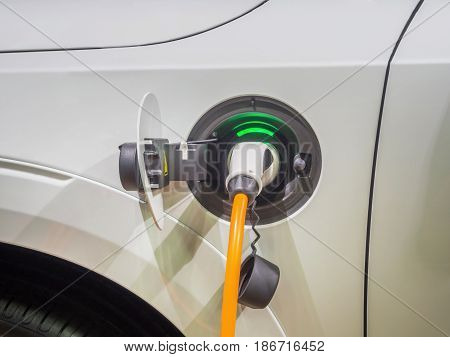 Charging an electric car with the power cable supply plugged in