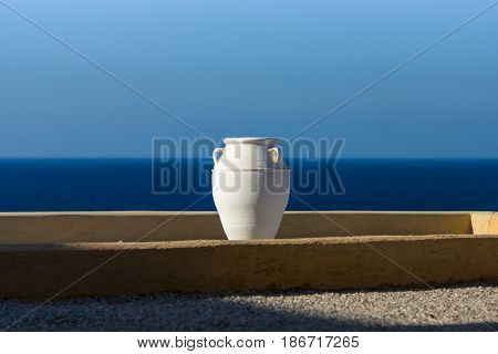 Typical view of the Mediterranean region. Decorative white amphora on a background of blue sky and sea.