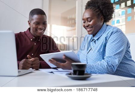Close up of two casually dressed African business coworkers sitting together at a table in a modern office working on a laptop and tablet