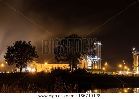 Petrochemical plant at night trees and a pond in the foreground. Tessenderlo Flanders Belgium Europe