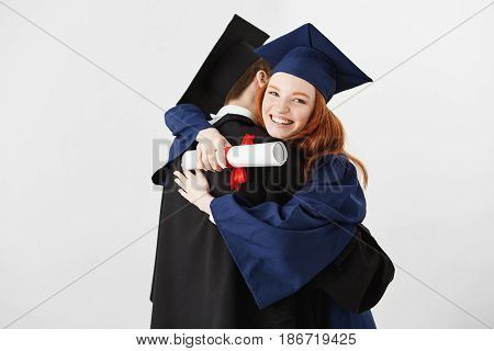 Two graduates embracing over white background. Ginger girl holding diploma smiling looking at camera.