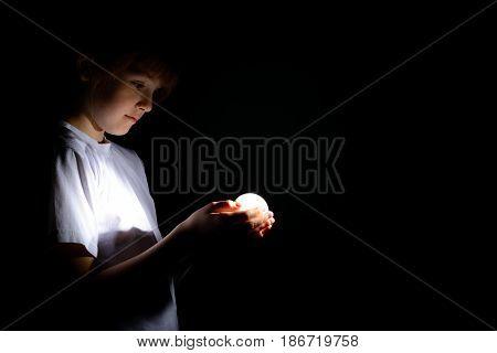 Cute Little Girl Holding A Luminous Led Light Bulb In The Dark