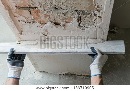Worker is putting a gypsum plaster on a brick wall.