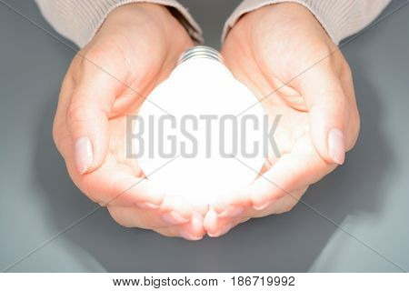 Female Hands Holding A Glowing Led Bulb