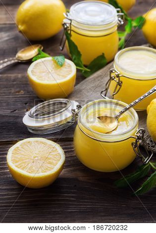 Fresh homemade lemon curd in glass jars on rustic wooden background. Selective focus.