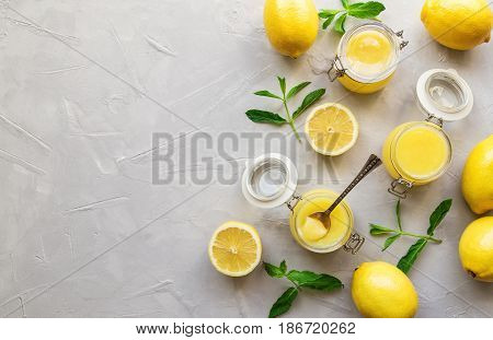 Fresh homemade lemon curd in glass jars on white concrete background. Top view. Copy space area.