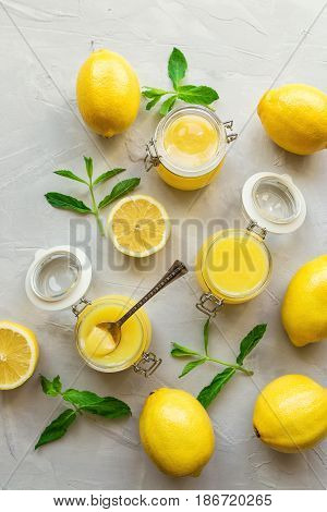 Fresh homemade lemon curd in glass jars on light concrete background. Top view.