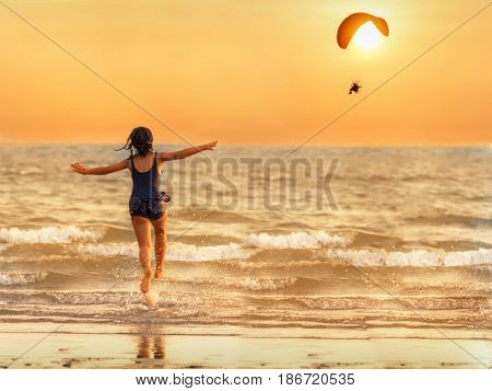 The girl runs into the sea pretending to parody the paramotor flying in the evening the sun is falling the concept of relaxation.