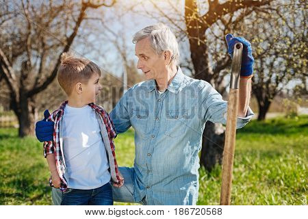 Family bonds. Senior man holding a shovel and standing on a knee while hugging his little grandson in a sunny day