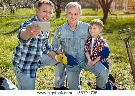 Capturing the moment. Three male generations outdoors snapping self portrait and enjoying the moment after gardening in a family backyard