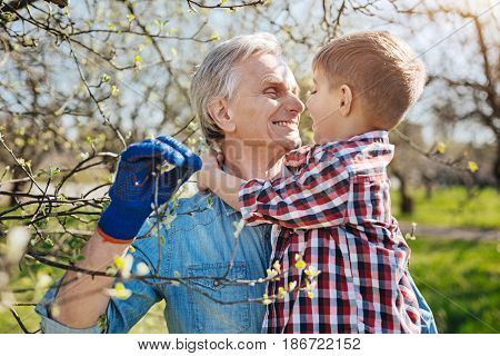Two peas in a pod. Radiant grandad grinning broadly while holding his grandson and spending a day gardening together