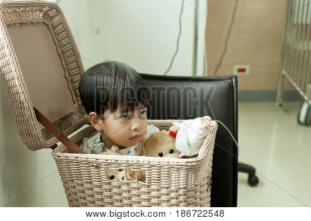 Children in hospital recuperating with his favorite teddy bear in the basket