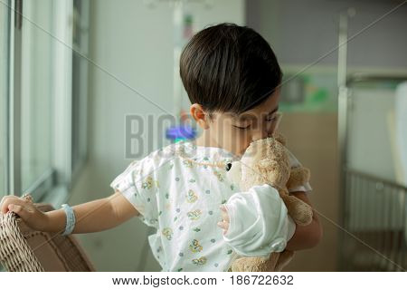 Children in hospital recuperating with his favorite teddy bear.