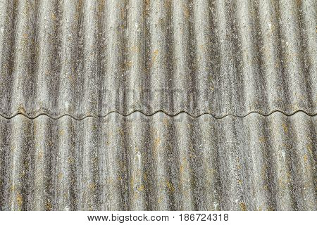 Asbestos cement sheets. Texture of old laid roofing sheets. Grey roof tiles.