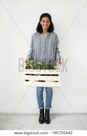Young beautiful african girl botanist smiling looking at camera holding box with plants over white wall.