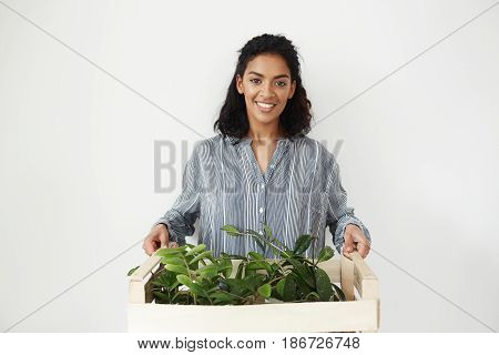 Young beautiful african girl botanist smiling looking at camera holding box with plants over white background. Copy space.