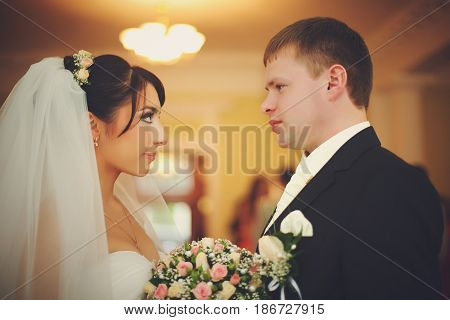 Bride And Groom Look At Each Other Attentively Standing In The Hotel Hall
