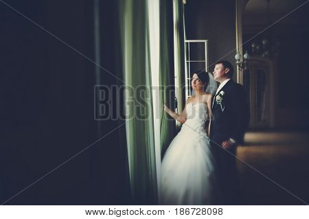 Bride And Groom Look Up In The Sky Through The Window