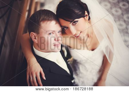 Bride With Hazel Eyes Looks Up Sitting On Groom's Knees