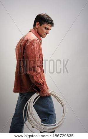 The hunky stud is looking down at his lasso.