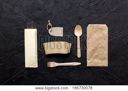 food delivery workdesk with paper bags and flatware on restourant dark table background top view mock-up