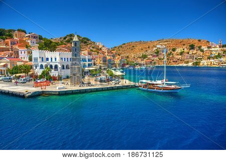 View on Greek sea Simy island harbor port, classical ship yachts, houses on island hills, tourists Aegean Sea bay. Greece islands holidays vacation travel tours from Rhodos island. Greece architecture