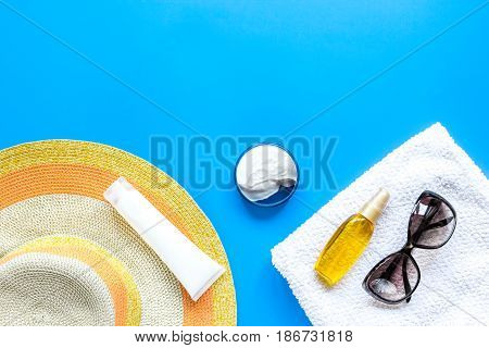 Summer rest with protiction cream, hat, towel on blue background top view space for text