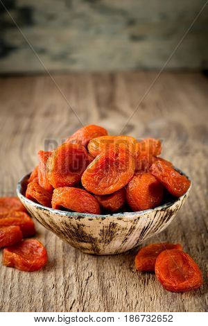 Dried apricots in a bamboo bowl on an old wooden background. Healthy dried fruit. Selective focus.