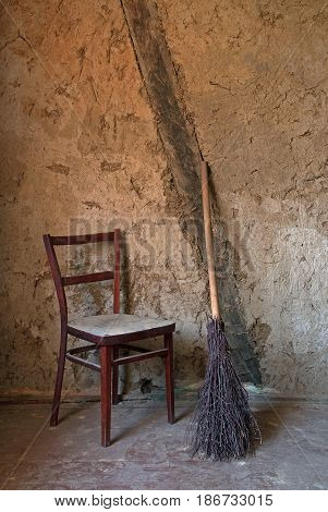 Old wooden chair and birch broom against a background of shabby walls. Sepia color dominates.