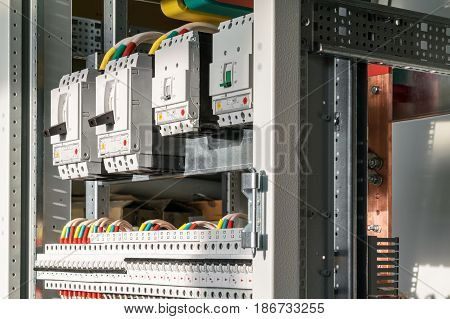 Connecting cables with cable lugs to circuit breakers in the electrical control panel on the artboard. Alignment of the components to ensure safety and reliability. poster