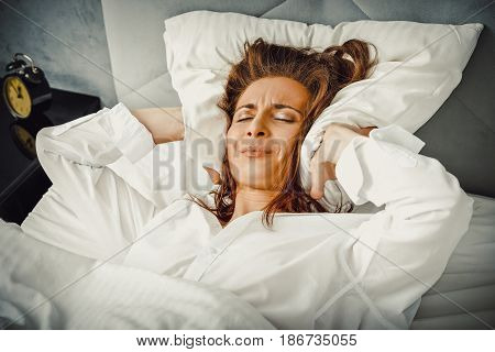 Woman covering ears with pillow because of noise. Insomnia concept.