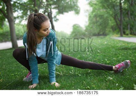 Portrait of young and sporty woman in sportswear doing yoga or Stretching exercises outside at the park on green field on cloudy day, Dnipro, Ukraine. She is sitting on the green meadow between trees and stretching her leg during exercise in grass right b