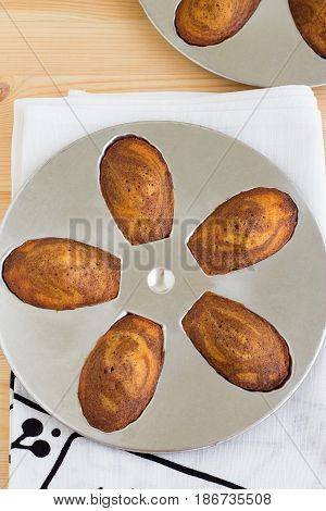 Traditional french cookies madeleine shell-shaped on special mold on the light wooden background. Vertical. Top view. Copy space
