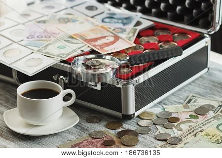 Collector's Coins And Banknotes, Magnifying Glass, Box For Coins And Cup Of Coffee