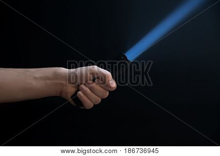 Male Hand Holding A Led Flashlight With A Narrow Blue Beam On A Black Background, Leaving The Left S