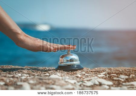 Female pressing ringing bell at the seaside. Summer vacation and travel concepts.